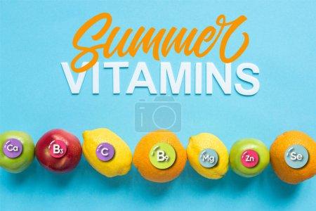 vue du dessus des fruits mûrs en ligne et illustration de vitamines d'été sur fond bleu