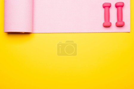 Photo for Flat lay with pink fitness mat and dumbbells on yellow background - Royalty Free Image