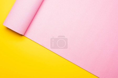 Photo for Top view of pink fitness mat on yellow background - Royalty Free Image