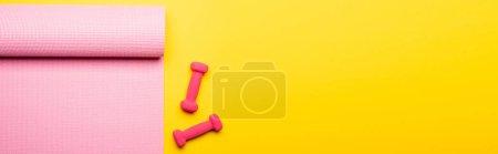 Photo pour Vue de dessus du tapis de fitness rose et des haltères sur fond jaune, vue panoramique - image libre de droit
