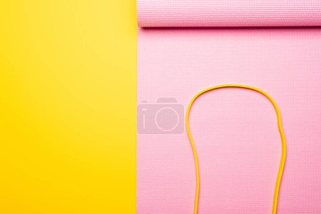 Photo for Top view of elastic band on pink fitness mat on yellow background - Royalty Free Image