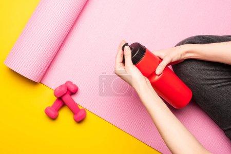 vue partielle d'une femme tenant une bouteille de sport assise sur un tapis de fitness rose près d'haltères sur fond jaune