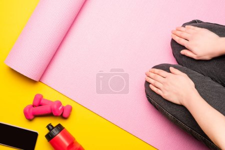Photo for Partial view of woman sitting on pink fitness mat near sports bottle, smartphone, dumbbells on yellow background - Royalty Free Image
