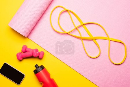 Photo for Top view of resistance band on pink fitness mat near smartphone, sports bottle, dumbbells on yellow background - Royalty Free Image