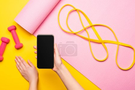 Photo for Cropped view of woman holding smartphone near resistance band on pink fitness mat and dumbbells on yellow background - Royalty Free Image