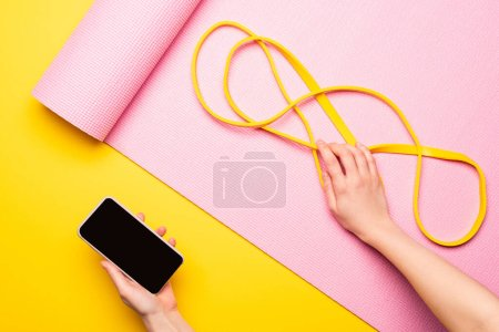 cropped view of woman holding smartphone and resistance band on pink fitness mat on yellow background