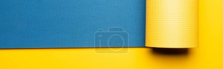 top view of blue fitness mat on yellow background, panoramic shot
