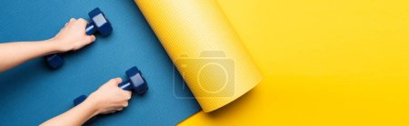 cropped view of woman holding dumbbells on blue fitness mat on yellow background, panoramic shot