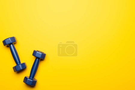 Photo for Top view of blue dumbbells on yellow background - Royalty Free Image