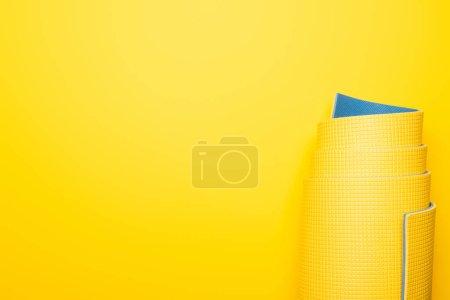 Photo pour Vue du dessus du tapis de fitness roulé sur fond jaune - image libre de droit