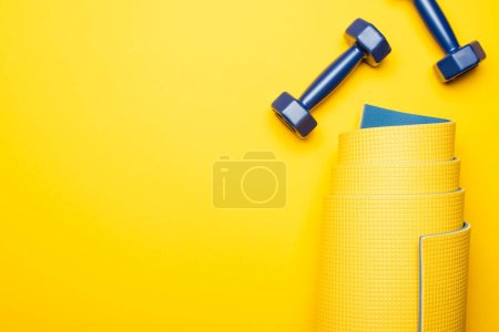 Photo for Top view of rolled fitness mat and blue dumbbells on yellow background - Royalty Free Image