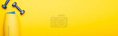 Photo pour Vue de dessus du tapis de fitness roulé et des haltères bleues sur fond jaune, prise de vue panoramique - image libre de droit