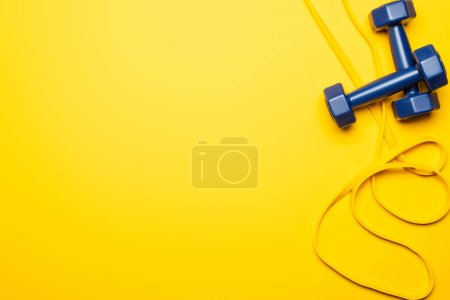 Photo for Top view of blue dumbbells and resistance band on yellow background - Royalty Free Image