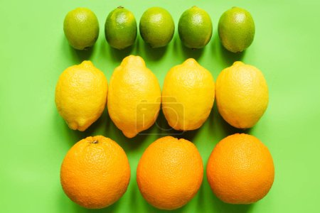 top view of ripe lemons, oranges and limes on green background