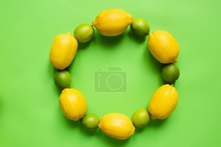 Photo for Top view of ripe lemons and limes arranged in round empty frame on green background - Royalty Free Image