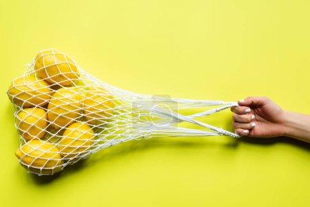Photo pour Vue recadrée de femme tenant des citrons entiers mûrs dans un sac à ficelle sur fond jaune - image libre de droit