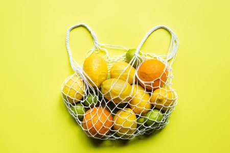 Photo for Top view of ripe whole citrus fruits in string bag on yellow background - Royalty Free Image