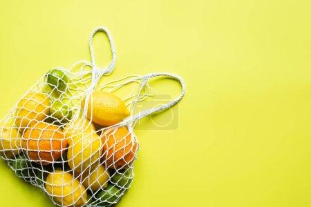 vue du dessus d'agrumes entiers mûrs dans un sac à ficelle sur fond jaune