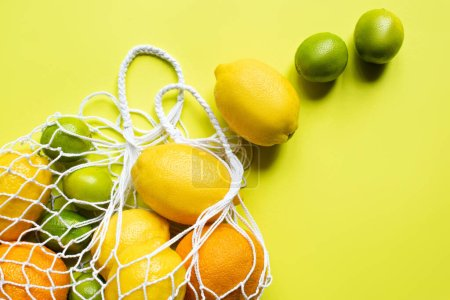 Photo for Ripe whole citrus fruits in string bag on yellow background - Royalty Free Image
