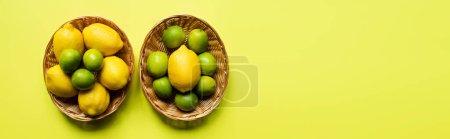 Draufsicht auf reife Limetten und Zitronen in Weidenkörben auf buntem Hintergrund, panoramische Ernte