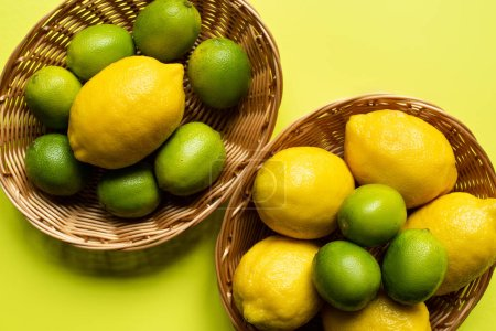 Photo for Top view of ripe limes and lemons in wicker baskets on colorful background - Royalty Free Image