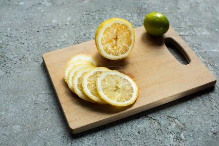 Photo pour Jaune mûr tranché citron et citron vert sur planche à découper en bois sur surface texturée en béton - image libre de droit