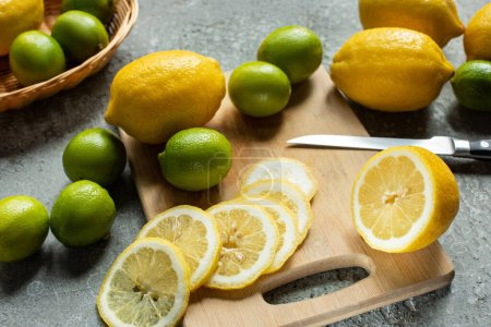 ripe yellow lemons and limes on wooden cutting board with knife on concrete textured surface
