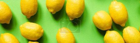 Photo pour Vue du dessus de citrons jaunes mûrs éparpillés sur fond vert, culture panoramique - image libre de droit