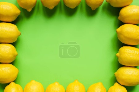 top view of ripe yellow lemons arranged in frame on green background with copy space