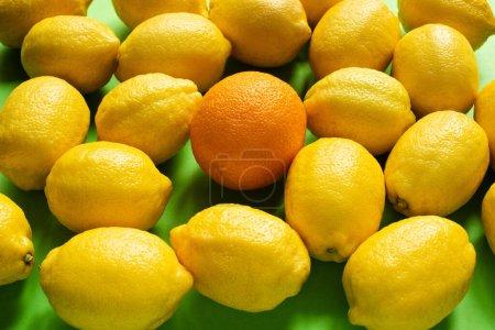 fresh ripe yellow lemons and orange on green background