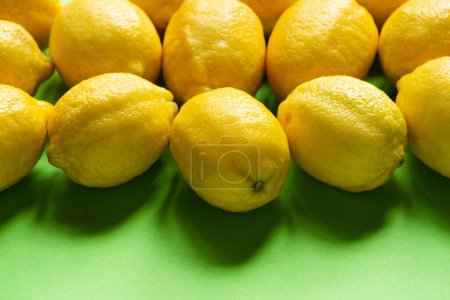 ripe yellow lemons on green background with copy space