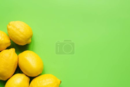 top view of ripe yellow lemons on green background with copy space