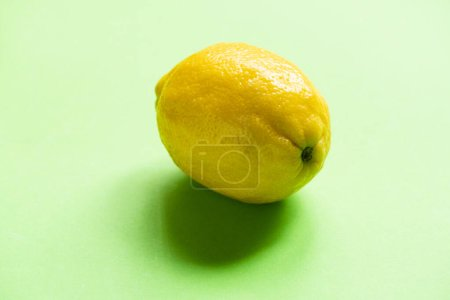 colorful ripe yellow lemon on green background