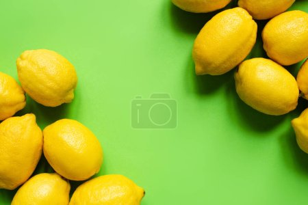 top view of ripe yellow lemons on green background