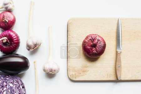 Photo for Top view of red onion, red cabbage, eggplant and garlic near wooden cutting board with knife on white background - Royalty Free Image