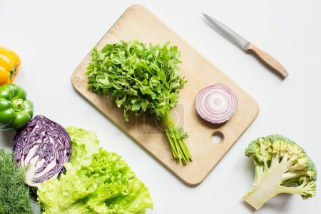 Photo for Top view of ripe vegetables near wooden cutting board with parsley and onion on white surface - Royalty Free Image