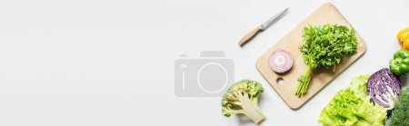 top view of ripe vegetables near wooden cutting board with parsley and onion on white surface, panoramic shot