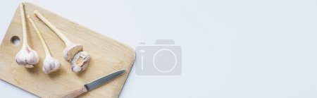 Photo for Top view of garlic on wooden chopping board with knife on white background, panoramic shot - Royalty Free Image