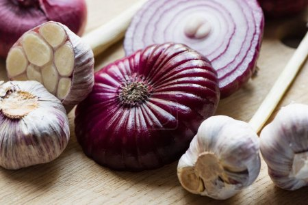 Photo for Close up view of red onion and garlic on wooden cutting board - Royalty Free Image