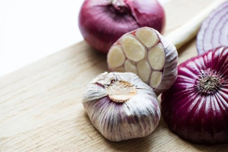 Photo for Close up view of red onion and garlic on wooden cutting board isolated on white - Royalty Free Image