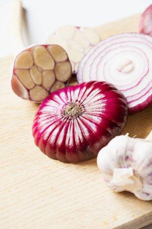 Nahaufnahme von roter Zwiebel und Knoblauch auf Holzschneidebrett auf weißem Hintergrund