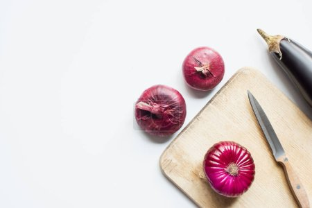 Photo for Top view of purple whole vegetables, knife and wooden cutting board on white background - Royalty Free Image
