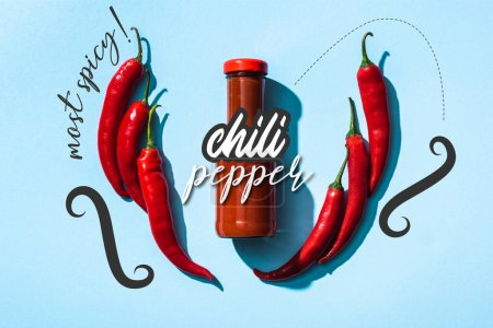 Photo for Top view of tomato sauce in bottle between chili pepper near most spicy lettering on blue - Royalty Free Image