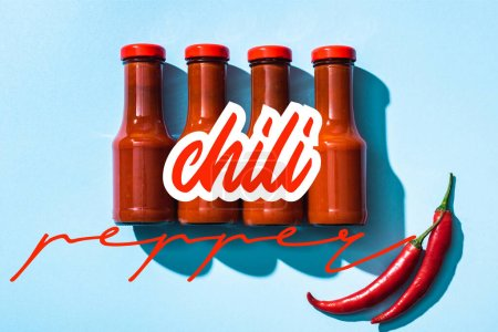Photo for Top view of chill pepper lettering near tomato sauce in bottles on blue background - Royalty Free Image