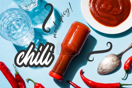 Photo for Top view of glasses with water, tomato sauce on plate and bottle beside chili peppers near most spicy lettering on blue - Royalty Free Image