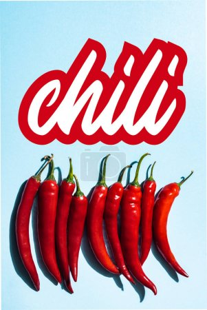 Photo for Top view of fresh and organic peppers near chili lettering on blue - Royalty Free Image