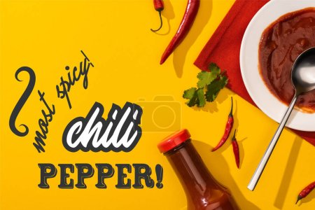 Photo for Top view of tomato sauce and cilantro near chili pepper and most spicy lettering on yellow - Royalty Free Image