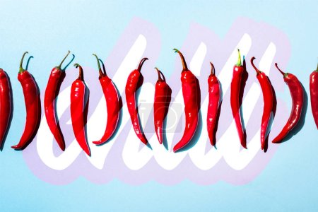 Photo for Top view of organic spicy peppers near chili lettering on blue - Royalty Free Image