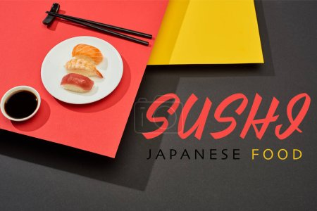 Photo for Fresh nigiri with salmon, shrimp and tuna near soy sauce, chopsticks and sushi japanese food lettering on red, yellow and black surface - Royalty Free Image