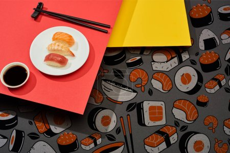 Photo for Fresh nigiri with salmon, shrimp and tuna near soy sauce, chopsticks and sushi illustration on red and yellow surface - Royalty Free Image